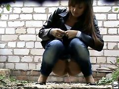 Hot chick in tight jeans peeing outside