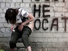 A la goth doing a pee behind a building