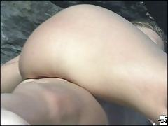 Hot close-ups of the nude butt and hips of a beach gal
